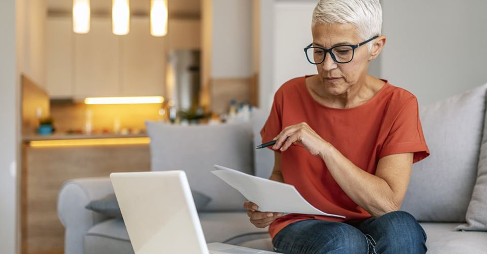 Older woman looks over paperwork at home on computer. H/t Edward Jones.