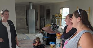 Brenda Kirk (left), executive director for local Habitat for Humanity affiliate, checks in on the progress Tuesday.