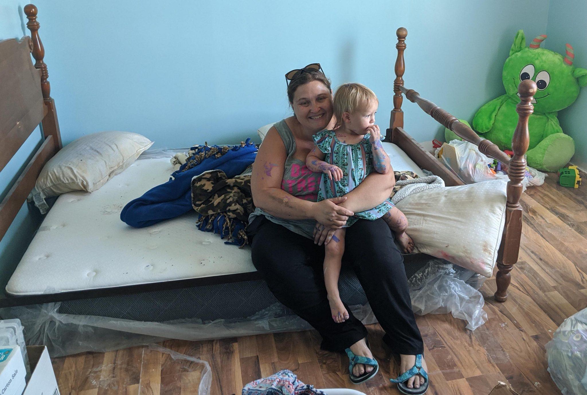 Jessica Meade holds her daughter Jarubia in her new bedroom.