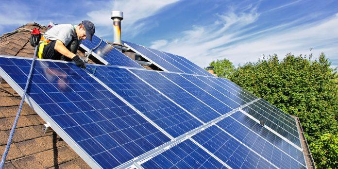Stock Image: Man installing alternative energy photovoltaic solar panels on roof
